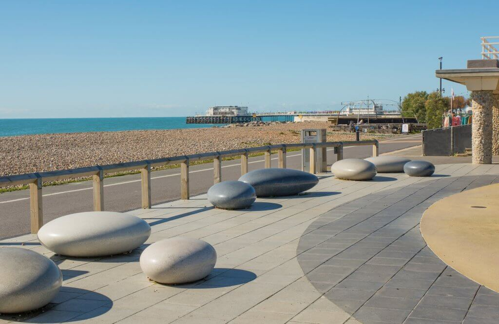 Seafront promenade and shingle beach at Worthing, West Sussex, England. Area known as Splash Point. Cafe and pier in background.